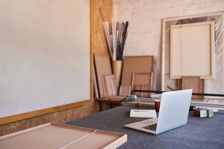 Laptop and mat cutter on a picture framing shop table