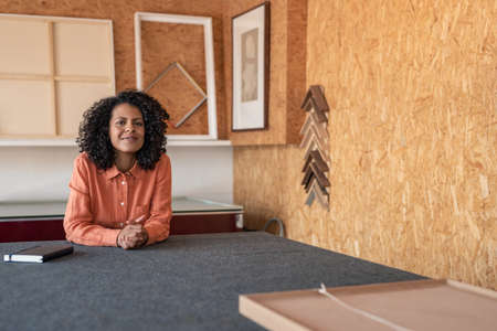 Portrait of a young woman with curly hair smiling while sitting at a work table in her picture framing studio