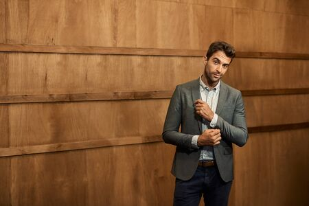 Stylish man in a blazer standing in a trendy lounge