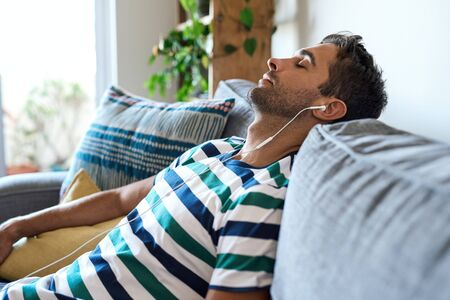 Young man listening to music on earphones on his sofa