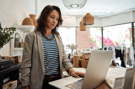 Young Asian woman working on a laptop in her boutique Stock Photo