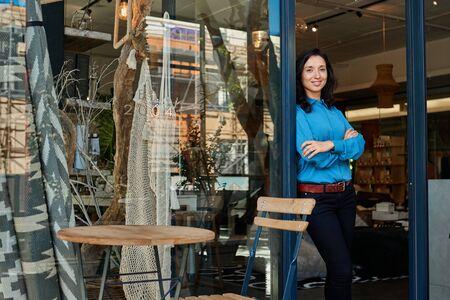Smiling Asian entrepreneur standing at the entrance of her boutique Foto de archivo