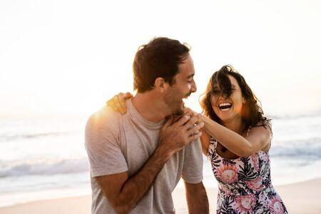 Laughing couple having fun together on a beach at sunset