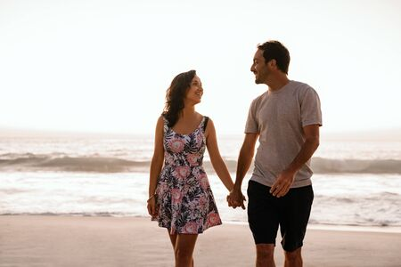 Young couple holding hands and walking along a sandy beach 免版税图像