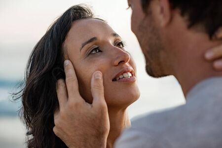 Loving woman staring into her husbands eyes at the beach