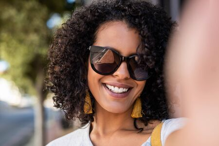 Smiling young woman standing in the city taking a selfie