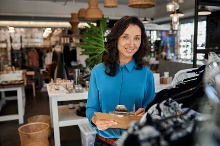 Smiling young Asian entrepreneur doing inventory in her clothing boutique 免版税图像 - 148927624