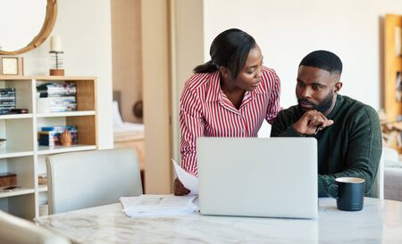 Young African American couple paying bills online with a laptop 免版税图像 - 148927631