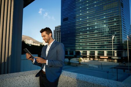 Smiling businessman standing on an office terrace using a tablet 免版税图像 - 148359684