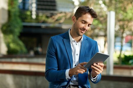 Smiling young businessman standing outside using a digital tablet 免版税图像