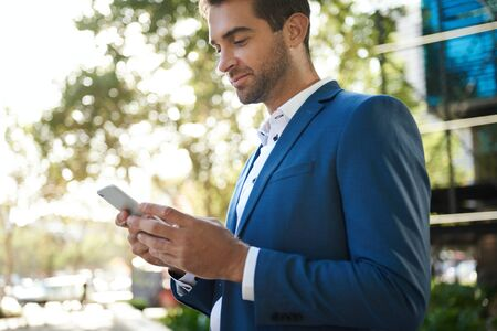 Young businessman standing outside sending a text on his cellphone 免版税图像 - 148927634