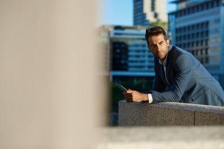 Businessman standing on an office terrace using a digital tablet 免版税图像 - 148927641