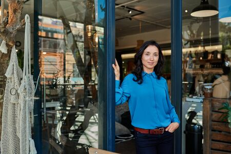 Smiling young Asian entrepreneur standing at her store entrance