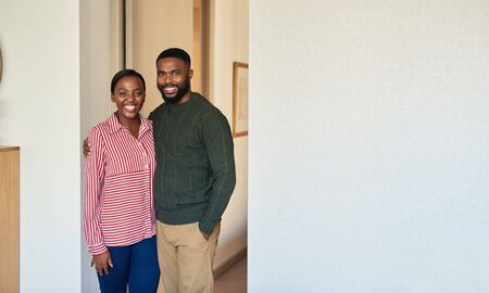 Smiling young African American couple standing together at home