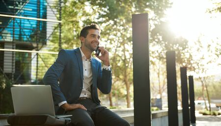 Smiling businessman talking on a cellphone outside his office building