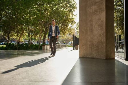 Stylish young businessman walking to work during his morning commute 免版税图像 - 148364187