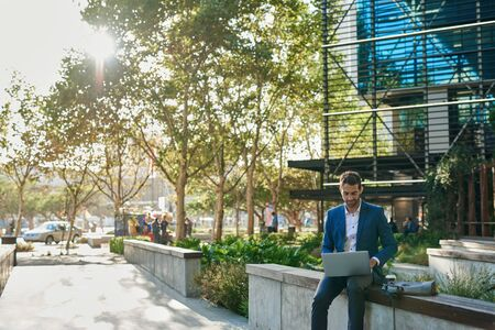 Businessman sitting on a bench outside and using a laptop