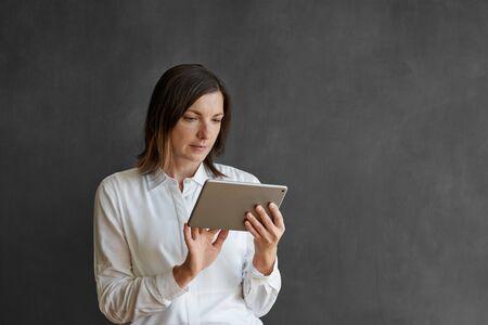 Businesswoman using a tablet in front of a blank chalkboard 免版税图像