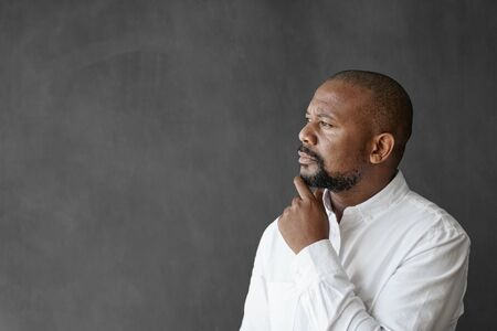 African American businessman standing by a chalkboard deep in thought