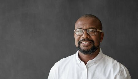 Smiling mature businessman in eyeglasses standing by a blank chalkboard 免版税图像