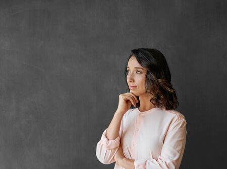 Young Asian businesswoman standing by a chalkboard deep in thought 免版税图像 - 149527446