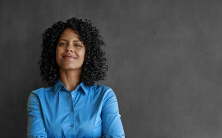 Smiling businesswoman standing by an office chalkboard 免版税图像