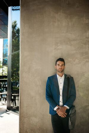 Stylish young businessman leaning against an office building wall outside