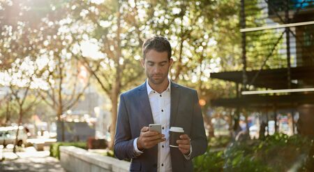 Businessman walking with a coffee and reading a cellphone message 免版税图像 - 149527455