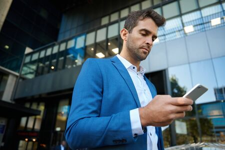 Young businessman reading a text message on his cellphone while standing in front of an office building in the city