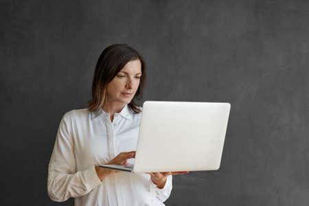 Businesswoman using a laptop in front of a blank chalkboard