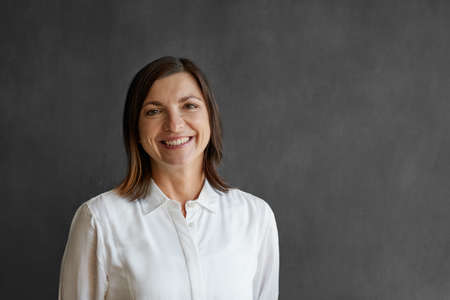 Smiling businesswoman standing in front of a blank office chalkboard