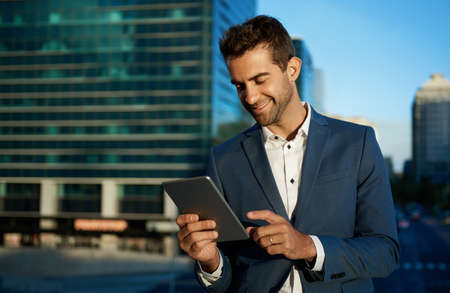 Smiling businessman working on a tablet on an office terrace 免版税图像