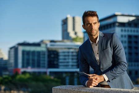 Businessman standing on an office terrace holding a digital tablet 免版税图像