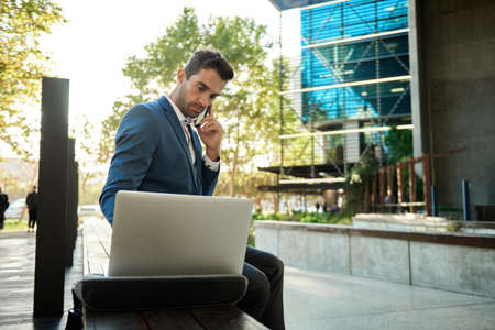 Businessman using a cellphone and laptop outside his office building