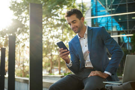 Smiling businessman sitting outside reading a message on his cellphone