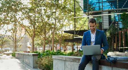 Businessman using a laptop while sitting outside his office building