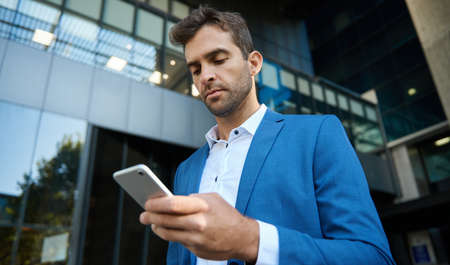Young businessman reading a text message on his cellphone