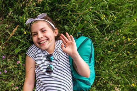 Cute little girl waving hi while lying on some grass 免版税图像