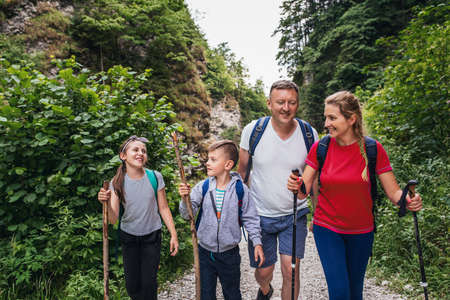 Smiling family of four hiking on a trail together 免版税图像 - 152066155