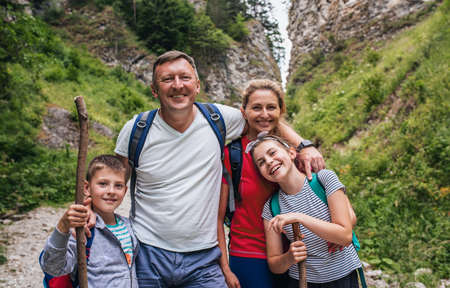 Smiling family standing together on a rugged trail while hiking