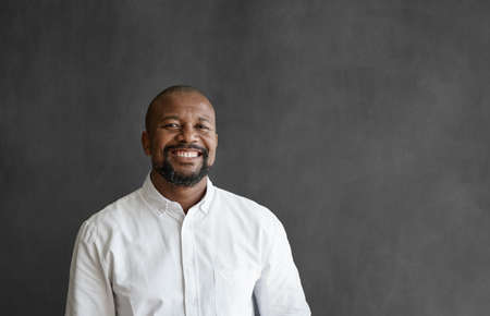 Smiling African American businessman standing in front of a chalkboard