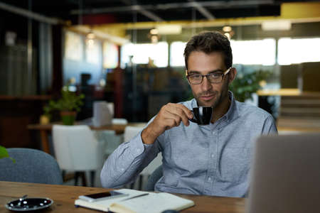 Young businessman drinking coffee at his office desk