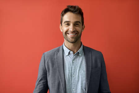 Smiling businessman standing in front of a red background Foto de archivo