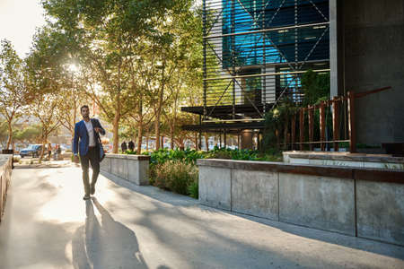 Stylish young businessman walking to work in the city Stok Fotoğraf
