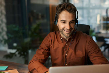 Smiling businessman talking on a headset with a client