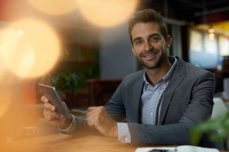Smiling businessman using a tablet in an office after work Stok Fotoğraf