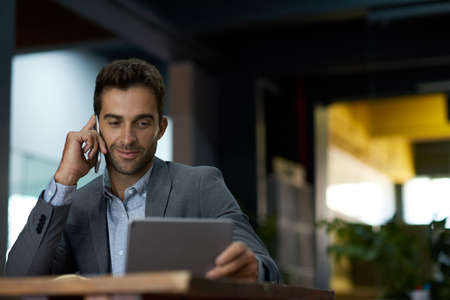 Businessman using a tablet and talking on his cellphone