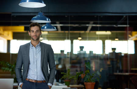 Confident young businessman standing alone in an office