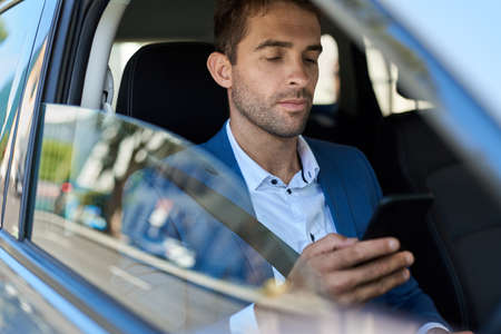 Man checking his cellphone while sitting in his car Imagens
