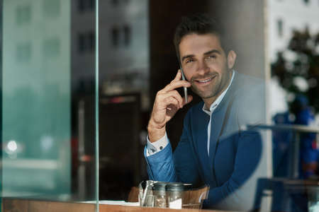 Young businessman talking on his cellphone inside of a cafe Stok Fotoğraf